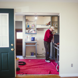 Landlord Carleton Winslow repairs cabinets in a single-family home he's renovating in Portland. Small residential renovation projects make up an estimated 60 percent of the permit applications that come into Portland City Hall.