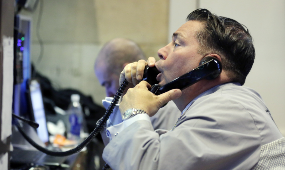 A trader uses a pair of telephones as he works in his post on the floor of the New York Stock Exchange on Friday.