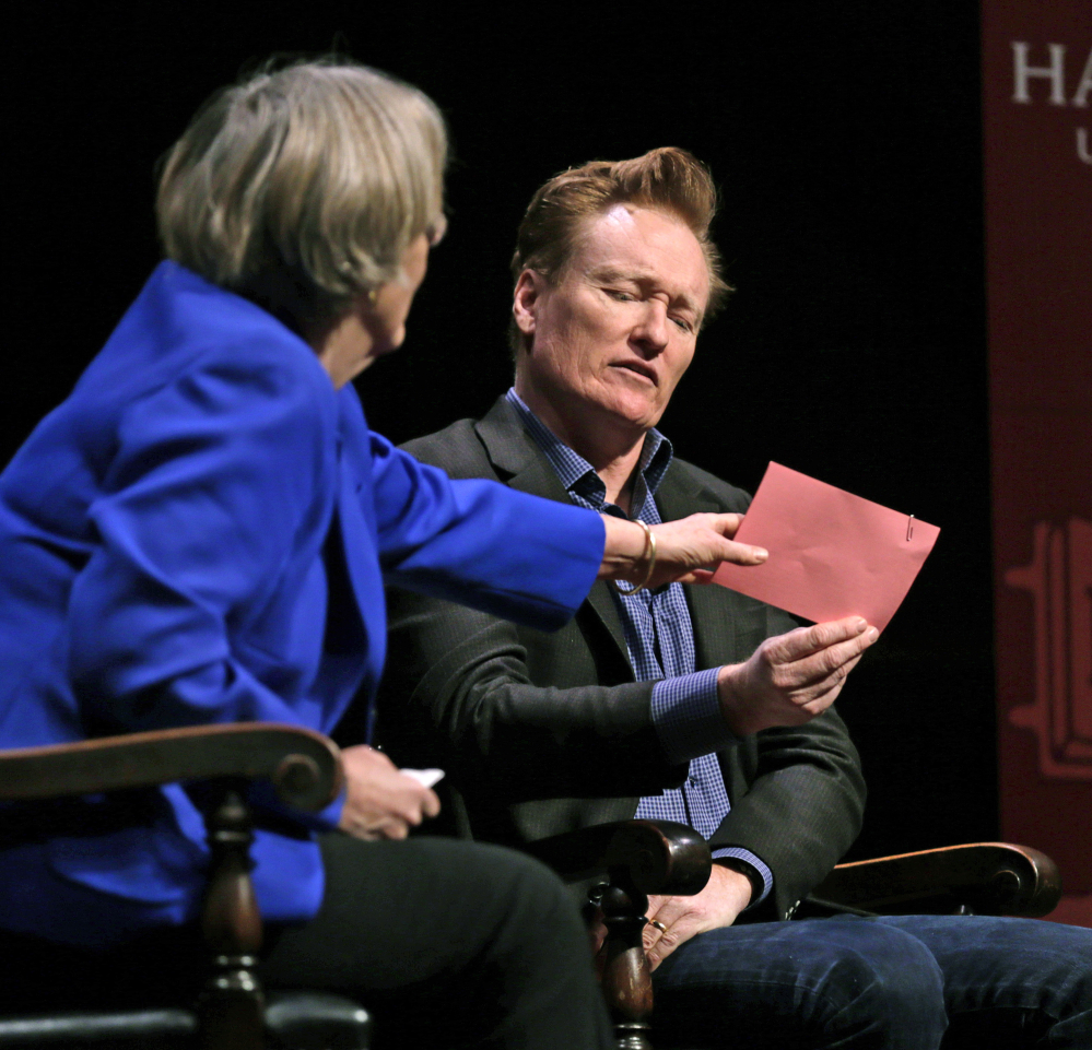 Television host Conan O'Brien sneaks a peek at prepared questions as Harvard President Drew Faust grabs them out of his hand at Harvard University on Friday.