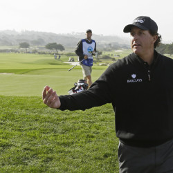 Phil Mickelson tosses his ball to the gallery after putting on the sixth green of the Monterey Peninsula Country Club Shore Course during the second round of the Pebble Beach Pro-Am on Friday in Pebble Beach, California.