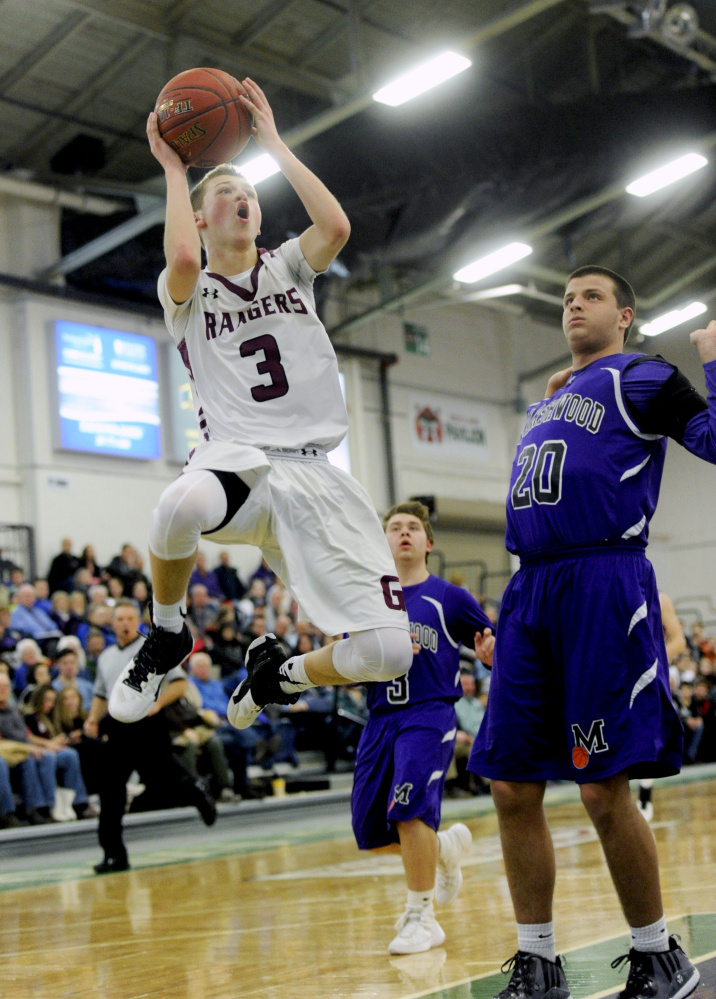 Derek Davis/Staff Photographer Jordan Bagshaw of Greely puts up a shot as Jack Spear of Marshwood avoids causing a foul during the second quarter.