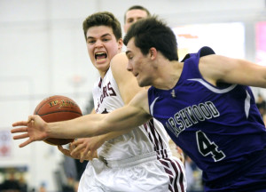 Zach Doyon of Marshwood reaches in to knock the ball away from Calvin Soule of Greely during the second quarter of Class A South boys' basketball quarterfinal final at the Portland Expo.