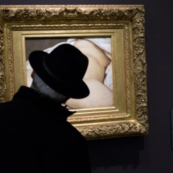 "A Musée D'Orsay visitor in Paris looks at ""The Origin of the World,"" the painting involved in a suit against Facebook."