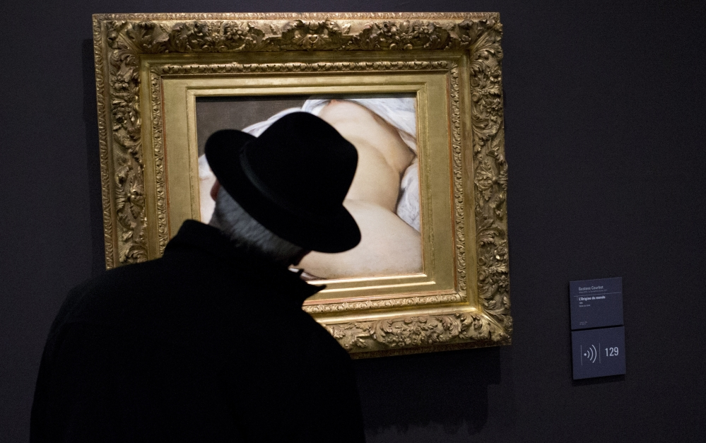 """A Musée D'Orsay visitor in Paris looks at """"The Origin of the World,"""" the painting involved in a suit against Facebook."""