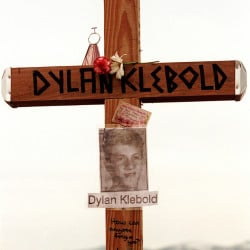"This April 28, 1999 file photo shows a cross bearing the name and likeness of Dylan Klebold and a message ""How can anyone forgive you?"" on a hill in Littleton, Colo., near Columbine High School where someone erected crosses to honor the dead."