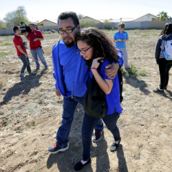 A father and daughter reunite in a vacant field, Friday, in Glendale, Ariz., after two students were shot and killed at Independence High School in the Phoenix suburb.