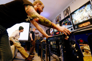 Tucker Daniels of Portland, sporting pinball tattoos, concentrates on a game of pinball as Matt Lodgek of Gorham, left, and Jerry Lindsay of Oakland take turns playing against each other during the IFPA Maine State Pinball Championship in Gorham on Saturday.