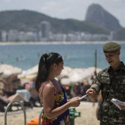A soldier explains how to combat the Aedes aegypti mosquito that spreads the Zika virus, on Copacabana beach in Rio de Janeiro, Brazil, on Saturday. More than 200,000 troops are part of the nationwide effort to eliminate the mosquitoes.