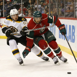 Boston left wing Brad Marchand, left, and Minnesota Wild defenseman Matt Dumba chase the puck during the second period of an NHL hockey game in St. Paul, Minn., Saturday. The Bruins won the game, 4-2.