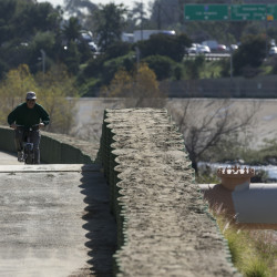 A cyclist rides along recently installed temporary flood control walls along the L.A. River in Los Angeles Friday, but the structures hardly seem necessary as much of the West Coast has just endured 10 days of record heat and no precipitation.