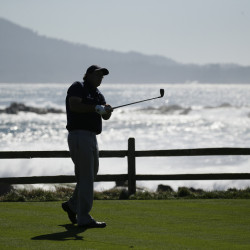 Leader Phil Mickelson is silhouetted as he hits from the 18th tee during the third round of the AT&T Pebble Beach National Pro-Am golf tournament Saturday at Pebble Beach, California.