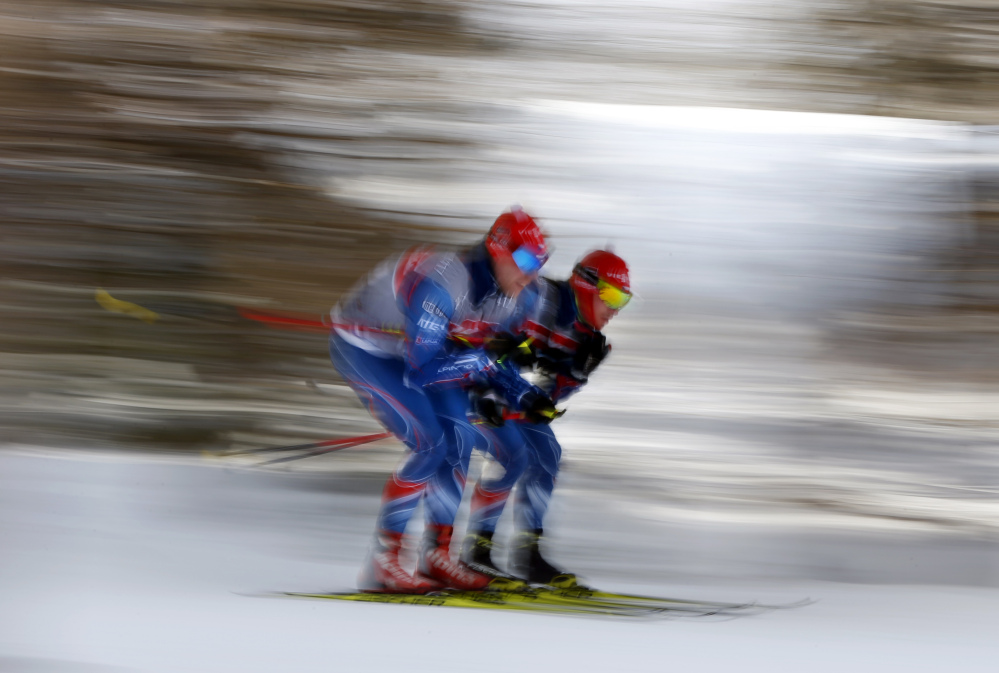 In this image taken with a slow shutter speed, members of the Czech Republic team glide together while testing wax and snow conditions prior to the relay competition at the World Cup Biathlon, Saturday, Feb. 13, 2016, in Presque Isle, Maine. (AP Photo/Robert F. Bukaty)