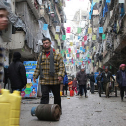 In this Thursday photo, civilians carry supplies in Aleppo, Syria.