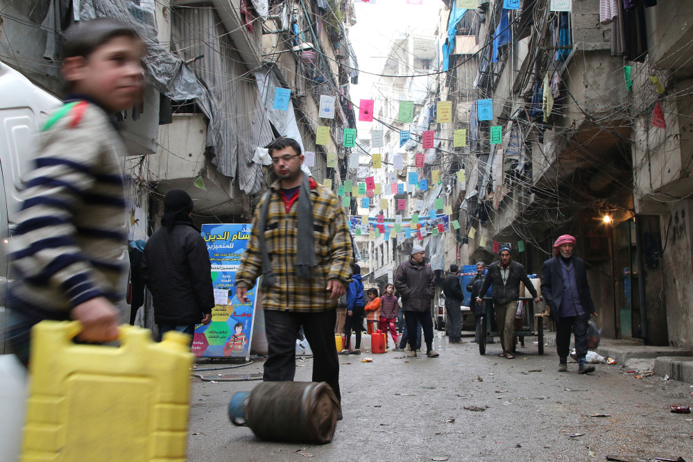 Civilians carry supplies Thursday in Aleppo, Syria.