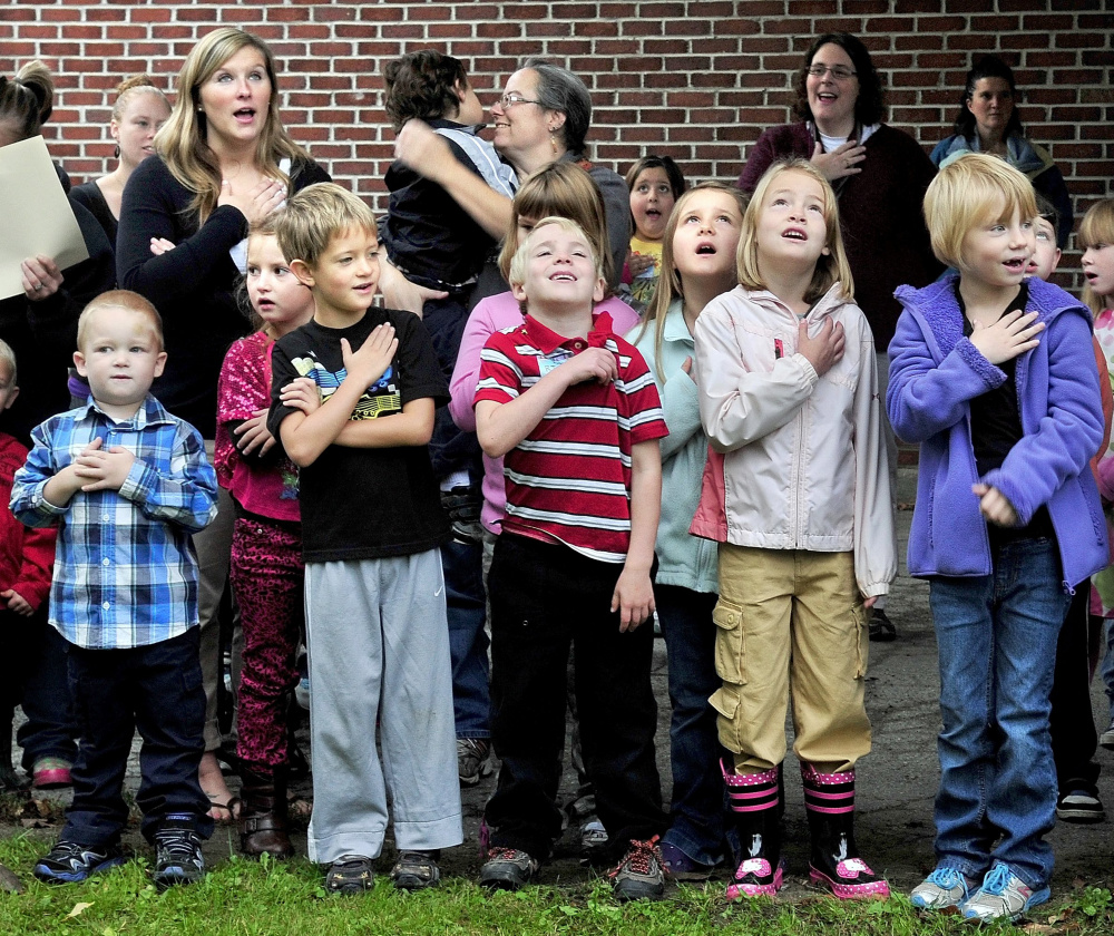 Students salute the flag in 2012 at the opening of the Cornville Regional Charter School, the state's first charter elementary school. The school is changing from an elected board to an appointed one as it seeks people with a wider variety of expertise to govern it.
