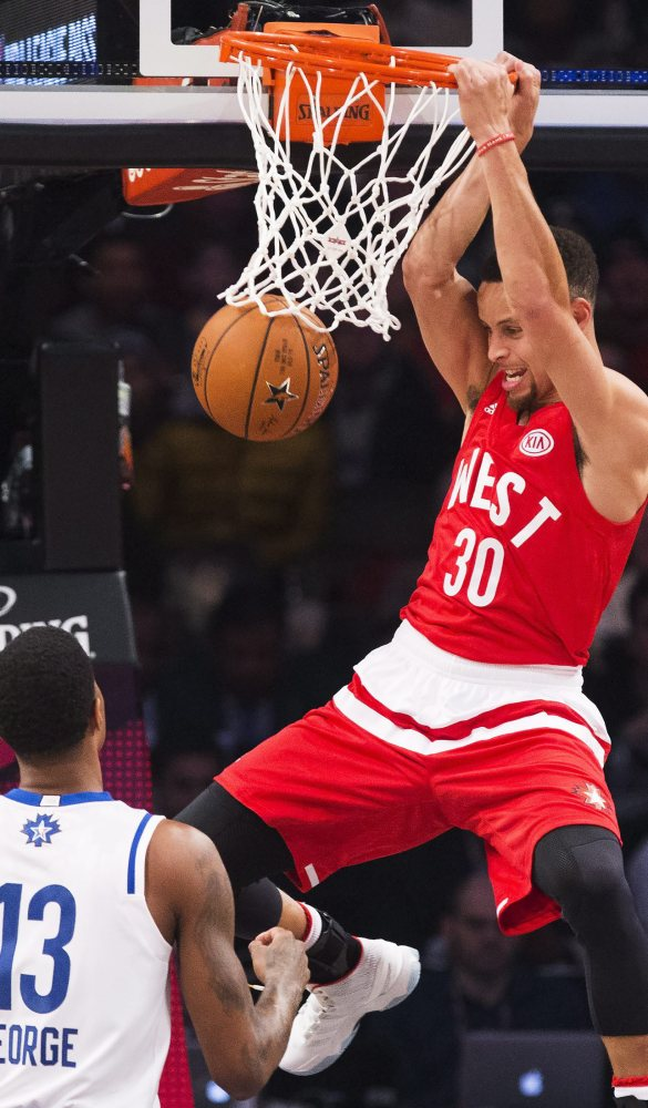 Golden State's Stephen Curry dunks in front of Paul George for two of his 26 points  in the Western Conference's 196-173 victory Sunday in Toronto.