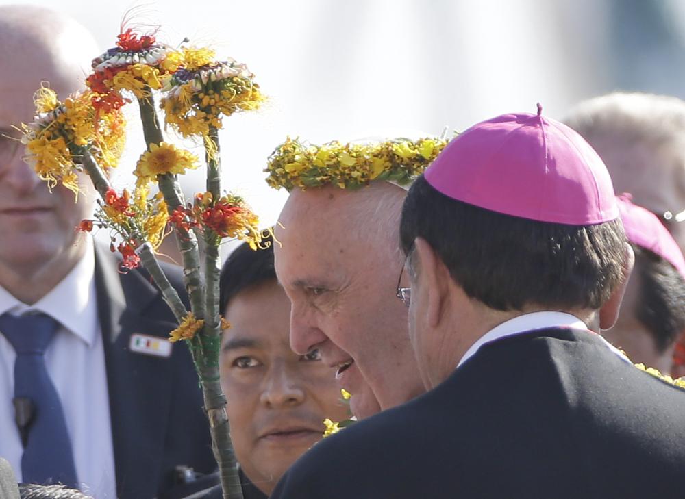 Pope Francis wears a crown of flowers, given to him by indigenous Mexicans, as he arrives at the airport in Tuxtla Gutierrez, Mexico, on Monday. Francis celebrated Mexico's Indians with a visit to Chiapas state, a center of indigenous culture, where he presided over a Mass.