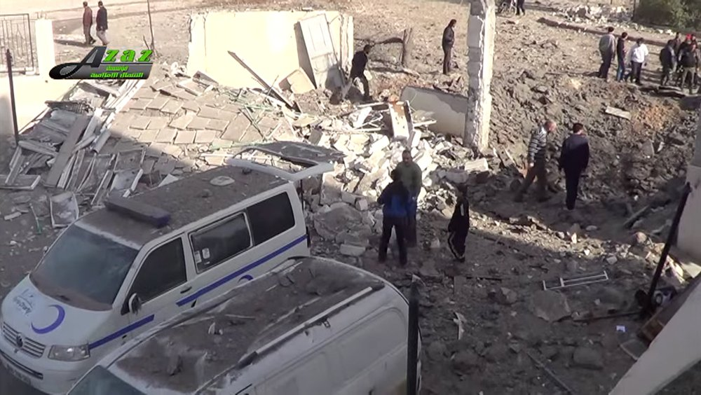 This image taken from video provided by the Syrian activist-based media group Azaz Media Center, which has-been verified and is consistent with other AP reporting, shows people gathered around destroyed vehicles in Azaz, Syria Syria, Monday.