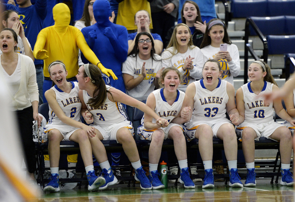 The Lake Region bench reacts after a teammate makes a free throw to take the lead in the closing seconds of their girls' basketball quarterfinal against Yarmouth on Tuesday at the Portland Expo. (Photo by Shawn Patrick Ouellette/Staff Photographer)