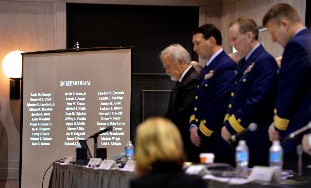 The investigative board stands for a moment of silence Tuesday for the crew members lost in the sinking of the El Faro. Bruce Lipsky/The Florida Times-Union via AP