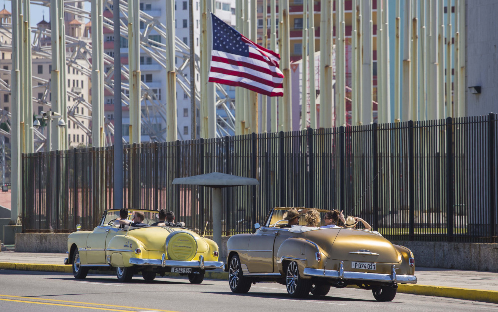 Tourists ride vintage American convertibles as they pass the U.S. embassy in Havana, Cuba, on Thursday. President Obama said that he will visit Cuba on March 21-22.