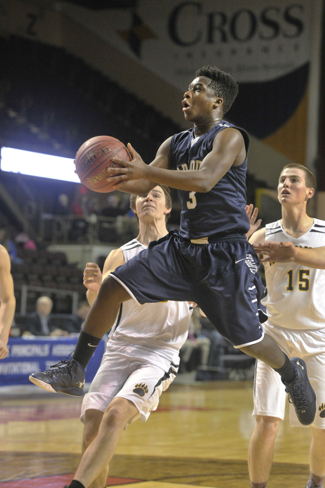 Yarmouth's Musseit M'Bareck goes in for a layup in front of Maranacook's Levi Emery, left, and Jason Brooks during their Class A South boys' basketball semifinal Thursday night at Cross Insurance Arena. Yarmouth won, 69-51.