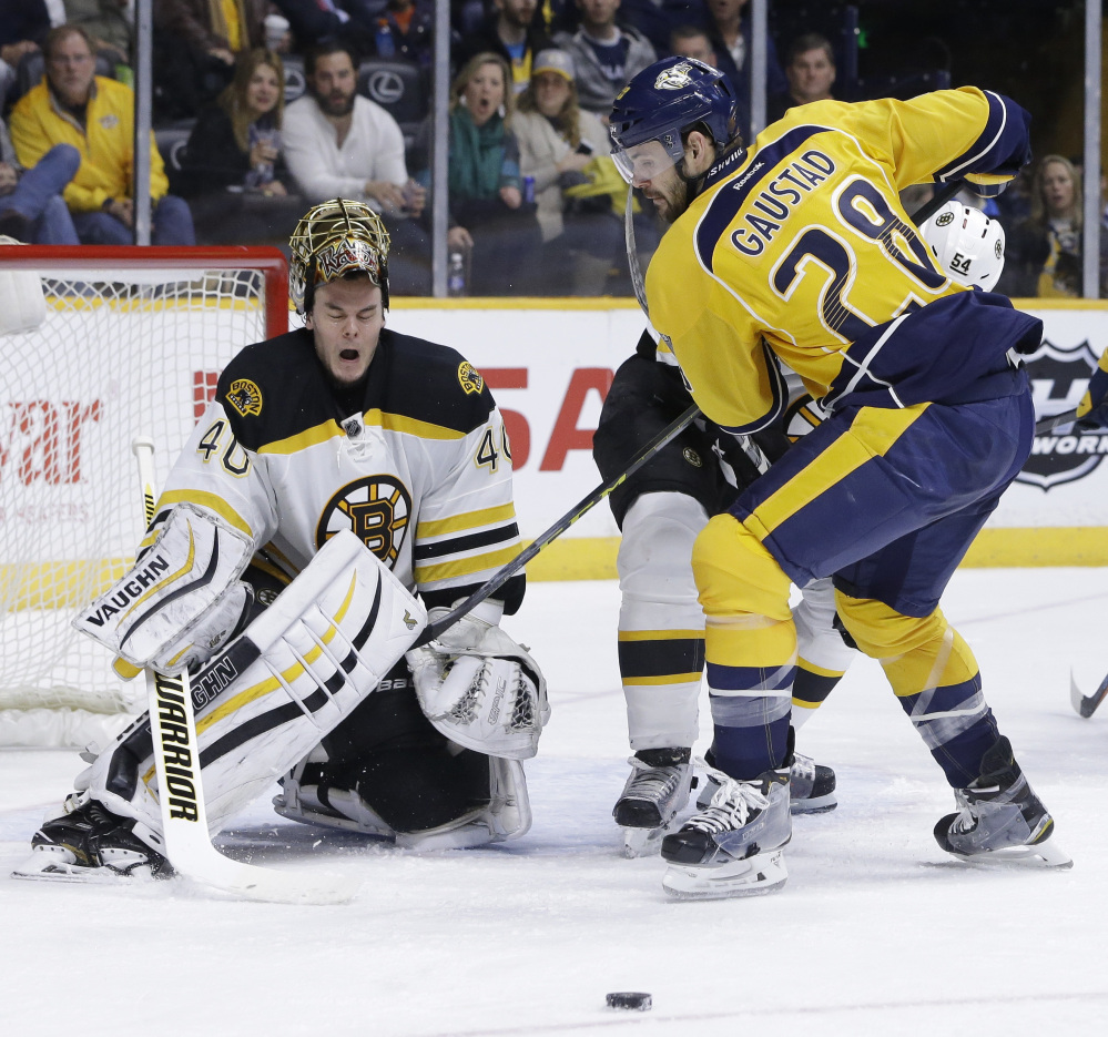 Bruins goalie Tuukka Rask loses his mask as Nashville's Paul Gaustad vies for the puck during in second period Thursday at Nashville, Tennessee.