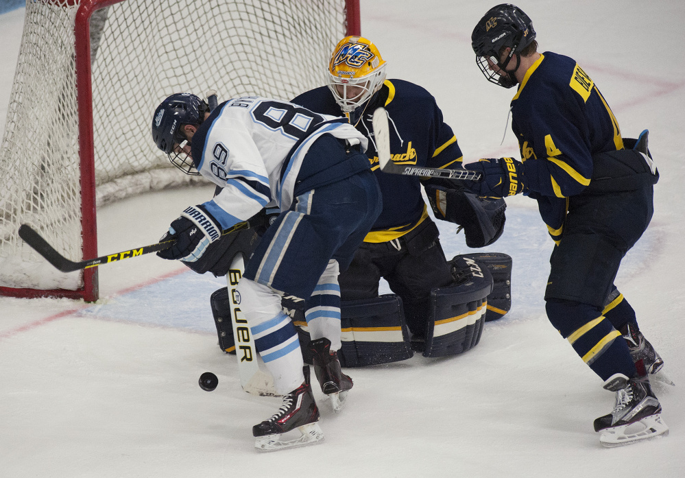 UMaine's Blaine Bryon gets a look at the goal before being denied by Merrimack's Collin Delia during second period action on Friday at Orono. Merrimack's Marc Biega also in on the play. Kevin Bennett Photo