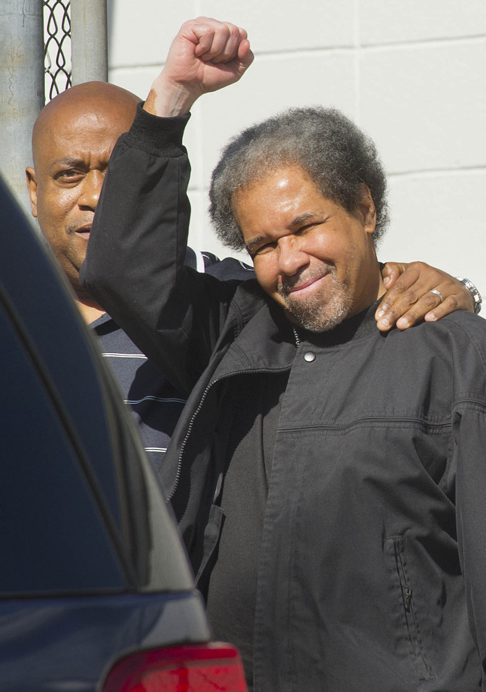 Albert Woodfox raises a clenched fist as he leaves prison with his brother.