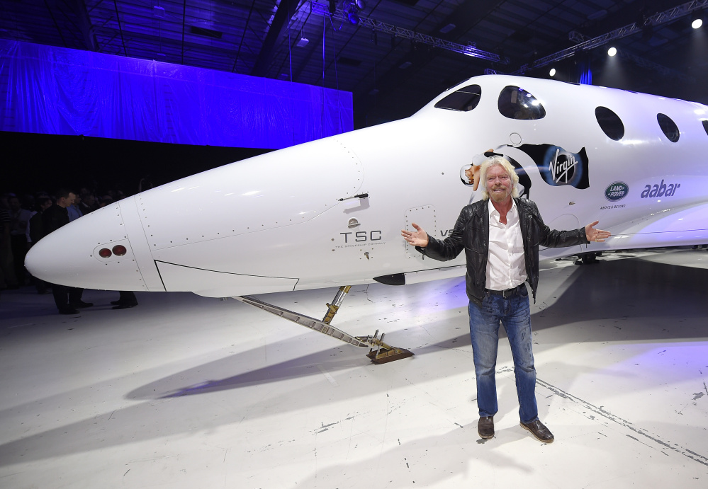 Sir Richard Branson stands in front of Virgin Galactic's SpaceShipTwo space tourism rocket after it was unveiled Friday in Mojave, Calif. The company is preparing to resume flight testing for the first time since a 2014 accident destroyed the original and killed one of its two pilots.