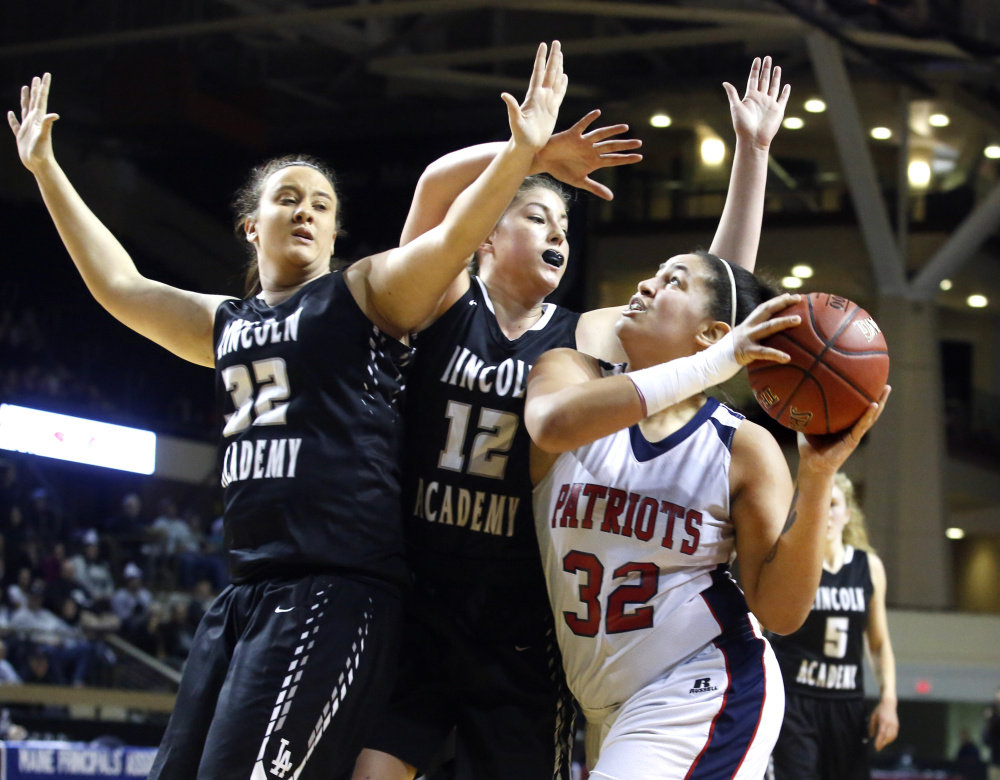 Brianna Genthner, left, and Avae Traina of Lincoln Academy try to block the path of Alanna Camerl of Gray/New Gloucester as she drives to the basket during the first quarter of the girls' Class B south regional final at Cross Insurance Arena on Saturday. Gray-New Gloucester will play Houlton for the state championship.