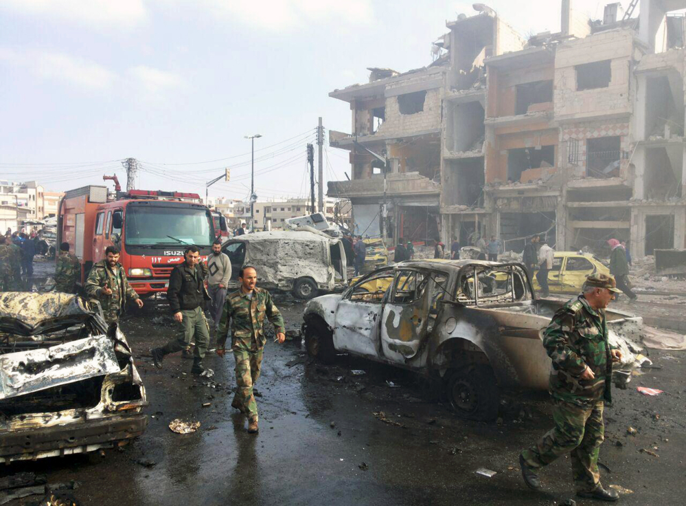In this photo released by the Syrian official news agency SANA, Syrian citizens gather at the scene where two blasts exploded in the pro-government neighborhood of Zahraa, in Homs province, Syria, Sunday.