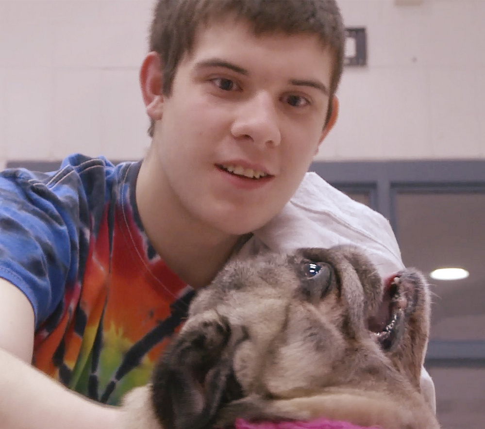 Kastan O'Dell, a resident at the Long Creek Youth Development Center in South Portland, enjoys a few moments with a pug named Cuppy as part of the facility's pet therapy program.