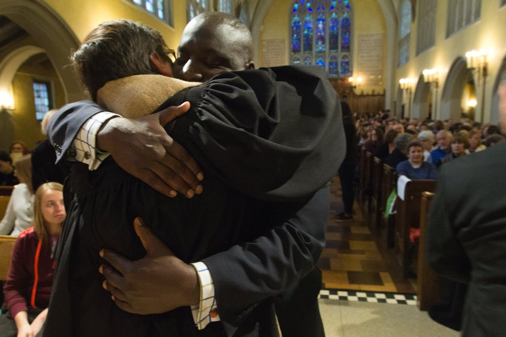 Mayor Bobby Hopewell hugs Rev. J Barrett Lee before the First Congregational Church candlelight vigil in remembrance of the mass shooting victims on Monday, in Kalamazoo, Mich.