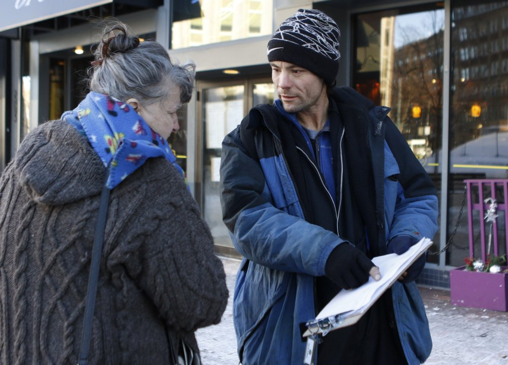 Brandon Scott, right, speaks with Joyce Lorraine as he works to collect signatures on a casino petition in Monument Square last month.