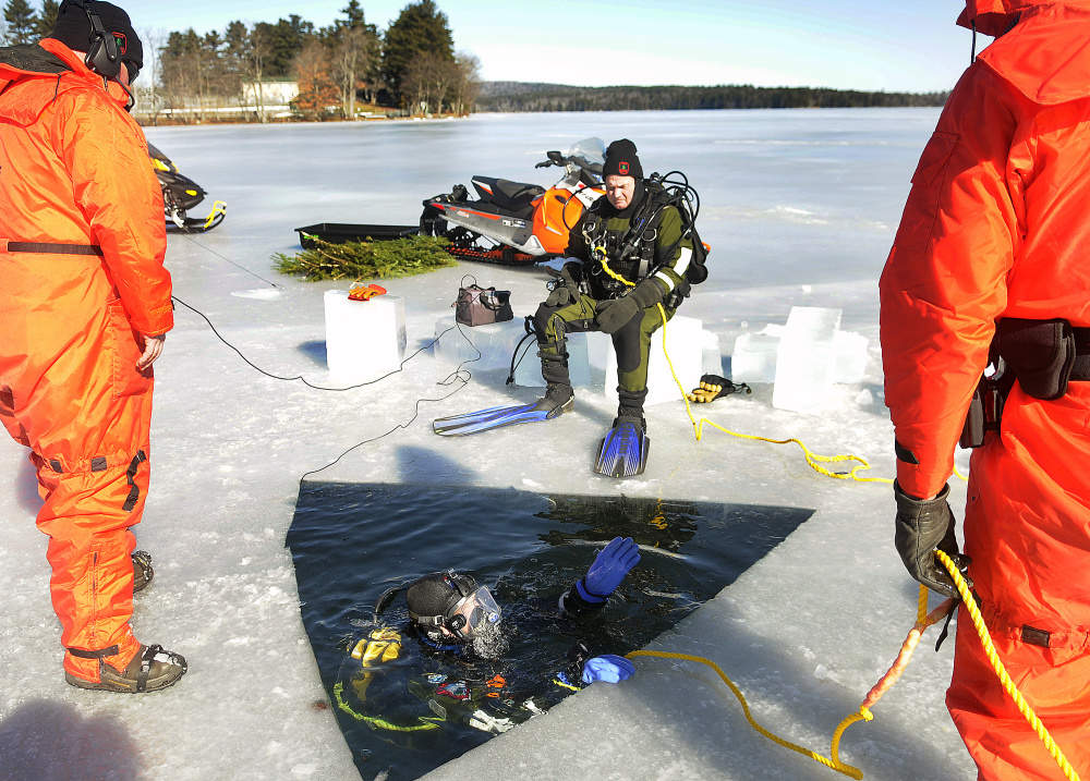 Game Warden Ethan Buuck discusses where he planned to search under the ice Monday on Salmon Lake in Belgrade with fellow members of the Maine Warden Service's dive team.