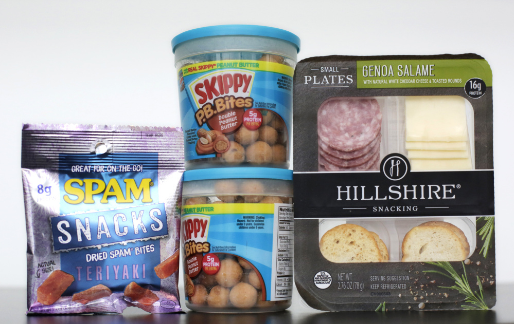 Spam Snacks, left, Skippy P.B. Bites, center, and Hillshire Genoa Salami with cheese and crackers are arranged for a photo, Wednesday, Feb. 24, 2016, in New York. As around-the-clock grazing upends the way people eat, companies are reimagining foods that aren't normally seen as snacks to elbow in on the trend. That means everything including grilled chicken, cereal, chocolate, peanut butter and Spam are now being marketed as snacks. (AP Photo/Mark Lennihan)