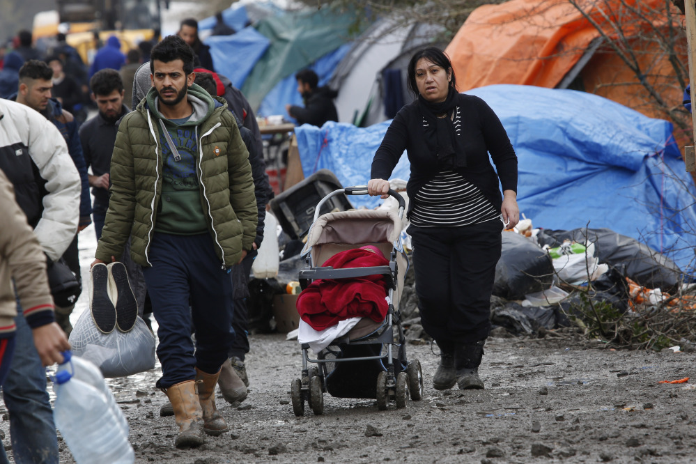 A migrant family walks in the mud at a makeshift camp in Grand-Synthe, near the town of Dunkerque, France, Wednesday.  More than 1,000 migrants live at the camp.
