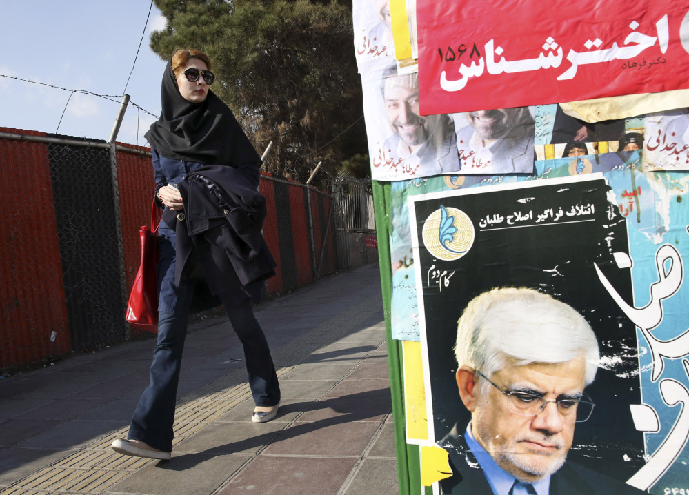 An Iranian woman walks past posters of candidates in Tehran on Thursday. Some 6,200 people are running for 290 seats in the nation's parliament, or Majles.