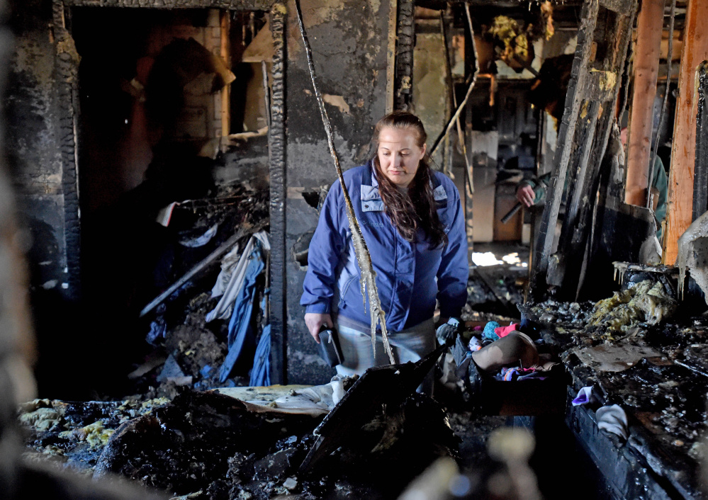 Hillary Barney, 24, looks through her belongings in her bedroom after a fire destroyed the apartment building where she lived in Cornville on Friday.