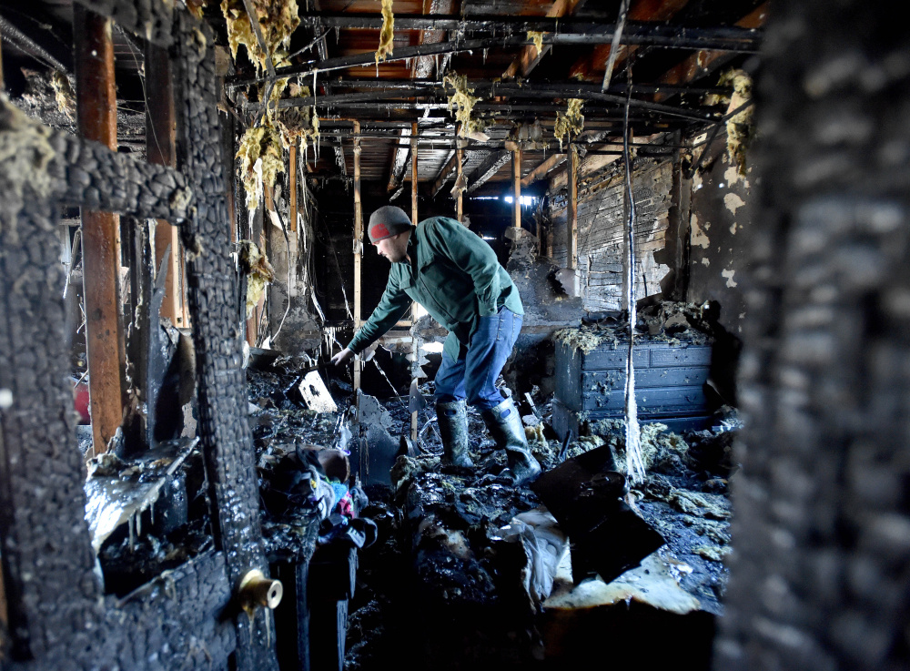 Scott Lessard, 28, looks through his first-floor apartment after narrowly escaping a fire in the early-morning hours in Cornville on Friday.