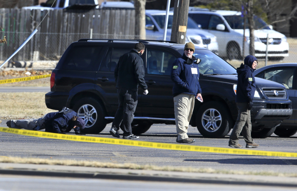 FBI agents search the parking lot at Excel Industries, the scene of Thursday's shooting in Hesston, Kan., on Friday. Harvey County Sheriff T. Walton identified the gunman as Cedric Ford, who stormed into the factory where he worked and shot 14 people.