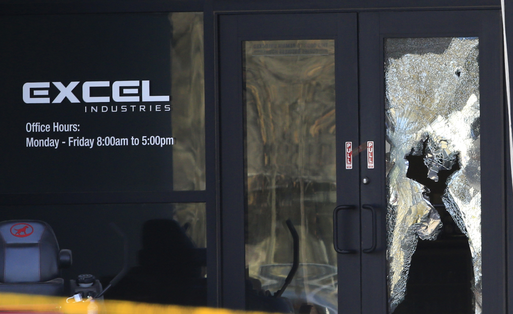 Shattered glass and bullet holes are seen at the front door of Excel Industries in Hesston, Kan., on Friday, a day after Cedric Ford stormed into the factory where he worked and shot several people.