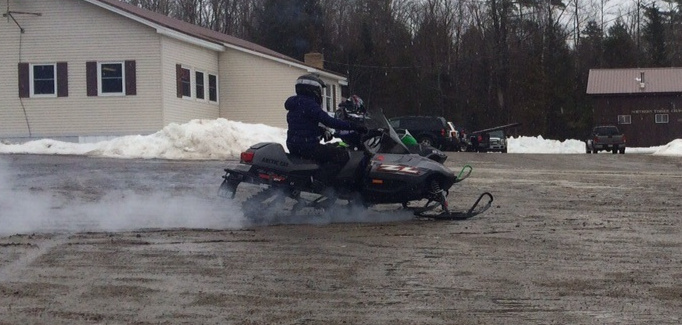 Snowmobilers ride from a parking lot outside the Northern Timber Cruisers Clubhouse, which usually is full of snow. A lack of snow and ample rain has left nothing but mud.