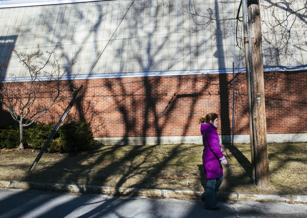 Heather Lippert walks past the Waynflete gymnasium Friday. The private school occupies 5 acres in one of Portland's most exclusive neighborhoods. Its long-term development plans have been watched closely by many residents in the West End. Whitney Hayward/Staff Photographer