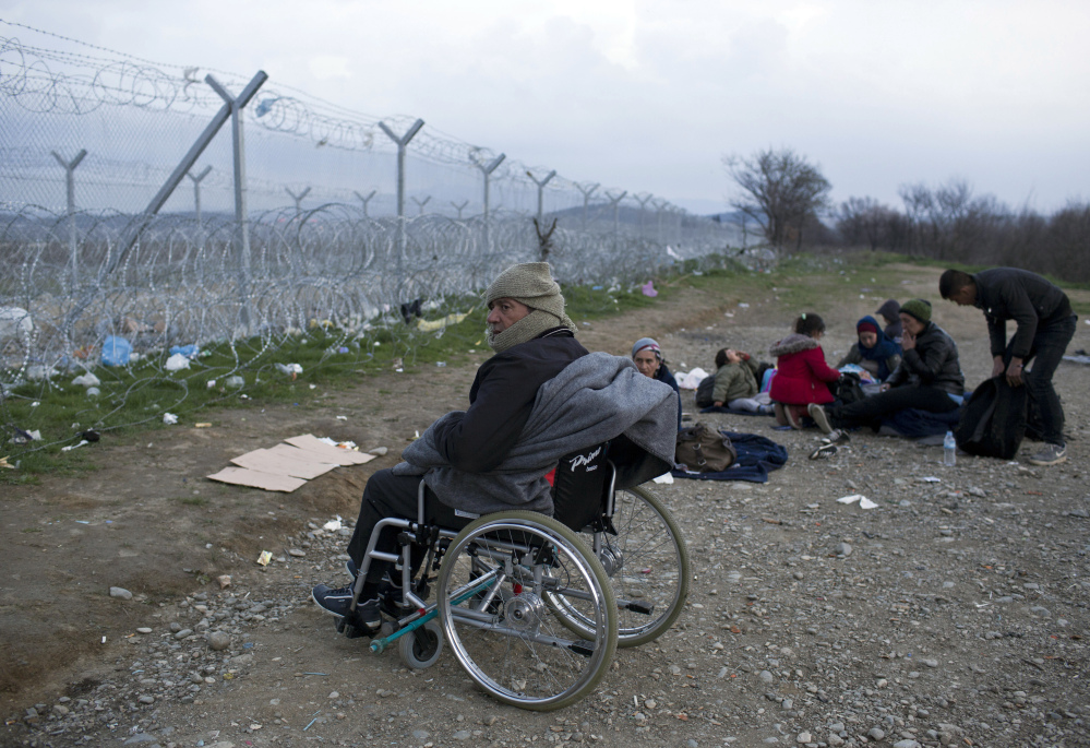 A stranded Syrian refugee on a wheelchair looks at the wire fence that separates Greece from Macedonia. Some European Union countries are taking unilateral action to shut down their borders to stem the flow of migrants.