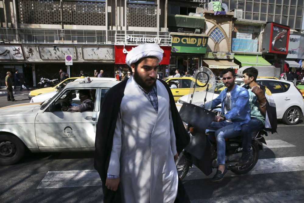 A clergyman crosses a square in central Tehran on Saturday, a day after elections in Iran.