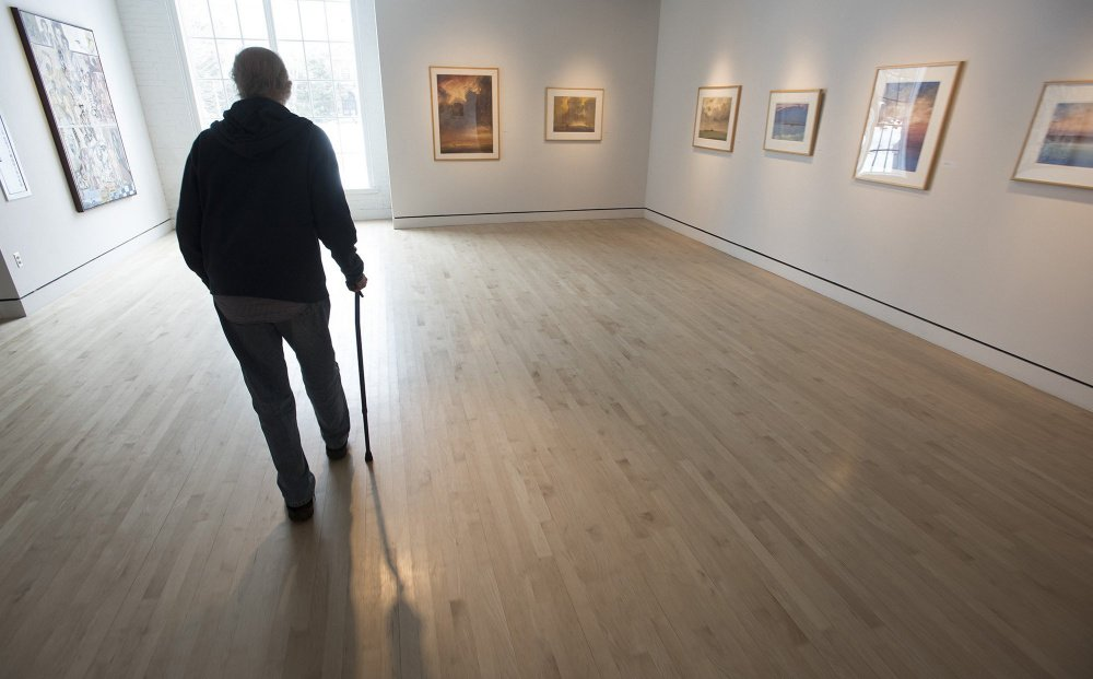 UMaine art instructor Michael Lewis walks through Lord Hall Gallery,