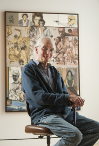 "UMaine art instructor Michael Lewis poses for a portrait at Lord Hall Gallery in front of ""Painter's Children,"" the earliest of 52 works of art on display from his 50-year career as an art teacher."