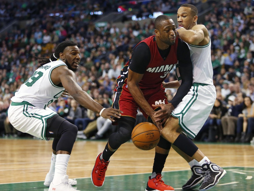 Miami's Dwyane Wade loses the ball while trying to cut between Boston's Jae Crowder, left, and Avery Bradley during the second half of the Celtics' 101-89 win Saturday in Boston.